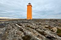 Icelandic landscape with orange lighthouse