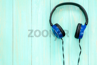 Stereo headphones on blue wooden background