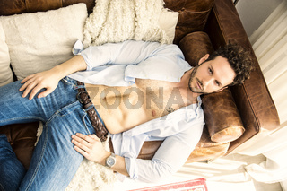 Shirtless sexy male model lying alone on couch
