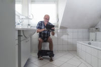 A pensioner sitting laughing on the toilet and surfing with a tablet on the Internet.