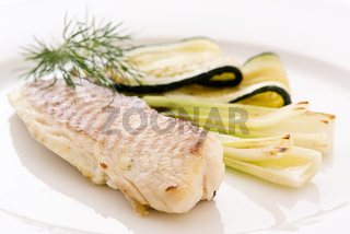 Tilapiini fillet with zucchini and leek as closep on a white plate