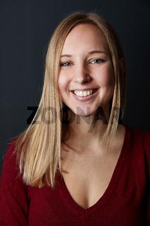 Glückliche junge blonde Frau lächelt