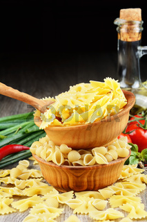 Raw conchiglie and farfalle pasta in the bowls