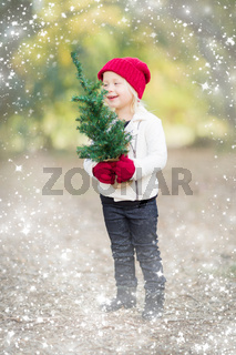 Baby Girl In Mittens Holding Small Christmas Tree with Snow Effect