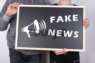 Schüler mit Schild Fake News