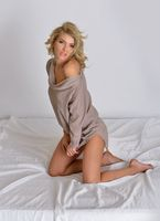 beautiful blonde woman in blouse lying in the bed