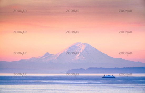 A ferry crossing the Puget Sound at sunrise with Mount Rainier, Washington, USA