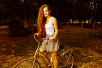 Young beautiful girl on a vintage bicycle in a fields vintage color look, copyspace
