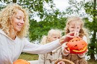 Kinder und Frau spielen mit Kürbis