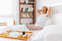 Happy elderly woman having breakfast in bed