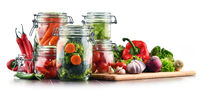 Jars with marinated food and raw vegetables isolated on white.