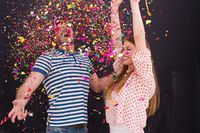 couple blowing confetti in the air isolated over gray