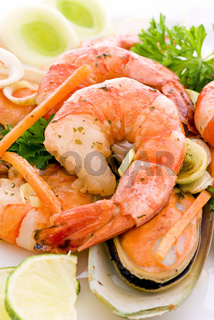Shrimps and mussels with vegetable as closeup on a white plate