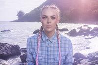 Young pretty girl with pink plaits between rocks