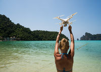 Drone in woman's hands over sea and blue summer sky