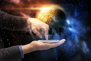 hands holding smartphone over planet in space