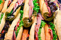 Sandwiches with vegetables and ham displayed in fast food restaurant.