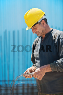 Construction worker cutting wire with pair of pliers