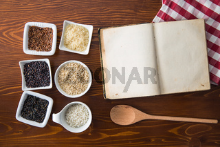 Blank cookbook and different rice varieties.