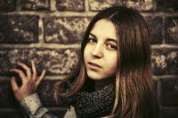 Young fashion teen girl at the brick wall