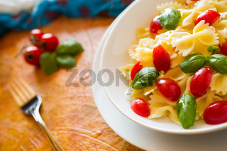 Closeup of Farfalle pasta with cherry tomatoes and basil over a colored background and fork