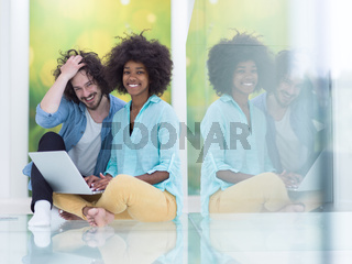 multiethnic couple using a laptop on the floor