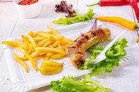 delicious grilled bratwurst with fries and mustard