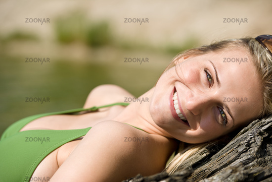 Blond woman relax in bikini at lake