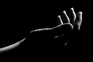 Human hand is drawn by light on a black background