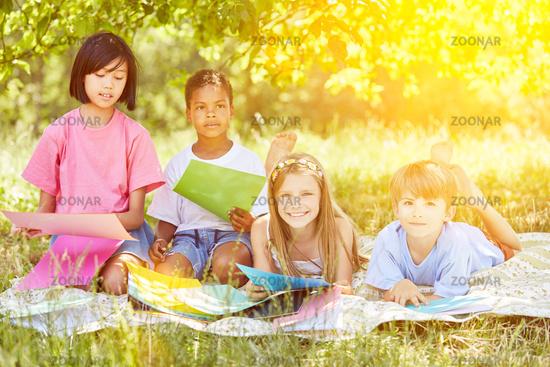 Gruppe Kinder beim Spielen und Basteln im Garten