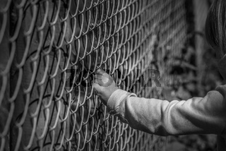 Little girl hand holding fence