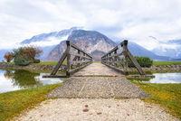 Wooden bridge leading to mountains