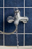 Chromium-plate tap with water flow out frozen in air front view on blue color tiled wall