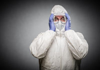 Man Holding Head With Hands Wearing HAZMAT Protective Clothing Against A Gray Background.