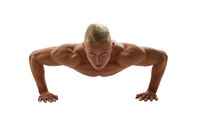 Naked bodybuilder posing while doing push-ups
