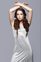 Beauty portrait of young woman with hands up. Brunette girl with long hair braides, and day female makeup on gray background