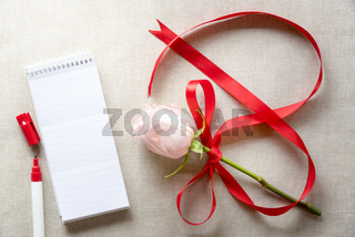 Rose with ribbon in shape of 8 and a notebook