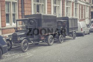 Zwei Oldtimer aus den 1920er Jahren stehen am Straßenrand.