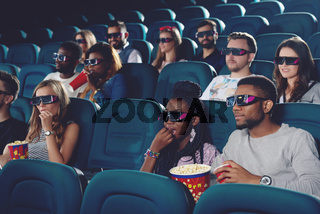 Group of africans and caucasians spending free time in cinema.