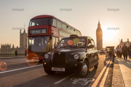 Traffic and random people on Westminster Bridge in sunset, London, UK.