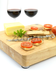 Savoury snacks on a wood cutting board isolated against a white background