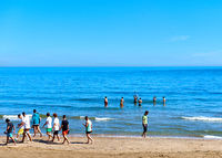 Crowd of people swimming and walking on the Marina d'Or beach. Spain