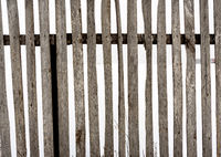 Old wooden fence in an aged and weathered state with a white snow background