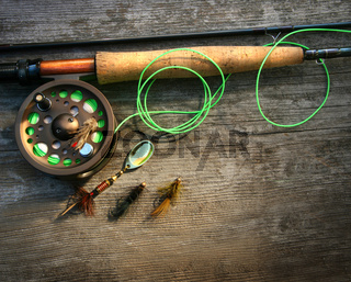 Fly fishing rod with polaroids pictures on wood