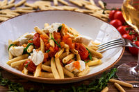 Vegetarian pasta garnished with tomato, cheese and fresh herbs