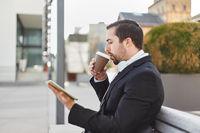 Mann trinkt Kaffee und schaut auf Tablet PC