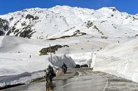 Zwei Motorradfahrer fahren auf der Passtrasse zwischen hohen Schneemauern über den Gotthardpass
