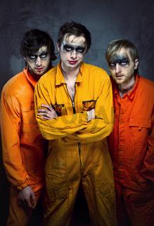 Three guys in orange uniforms