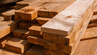 Stack of new wooden studs at a lumber yard warm color tone selective focus.