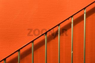Treppengeländer vor orangenen Wand